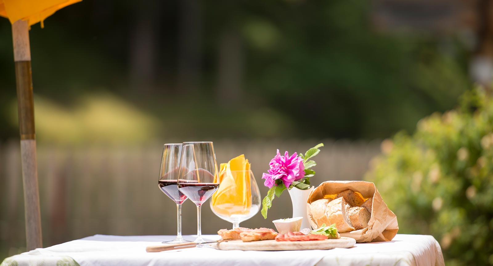 a breakfast table covered with snacks and wine in the garden of Lech da Sompunt