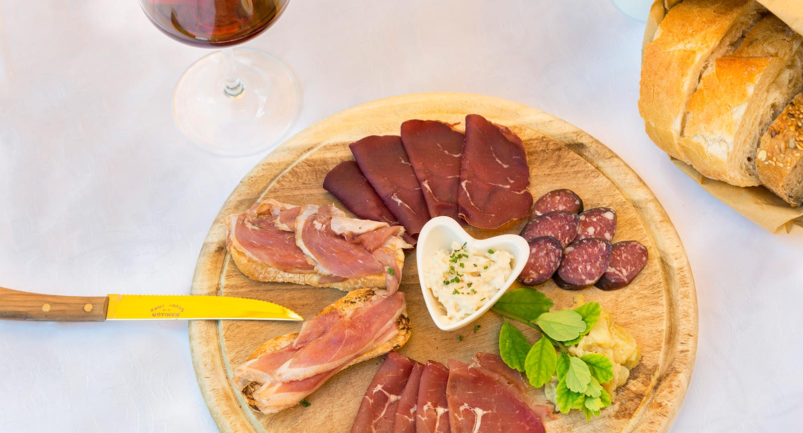 a cutting board with various meat slices and spread-cream
