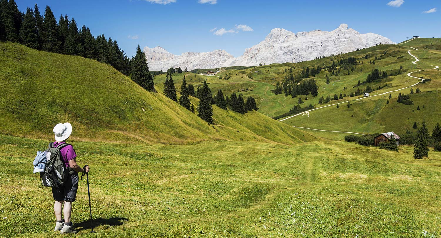 a lady with hat and walking sticks stands on the meadow and looks at the Dolomites during her hike