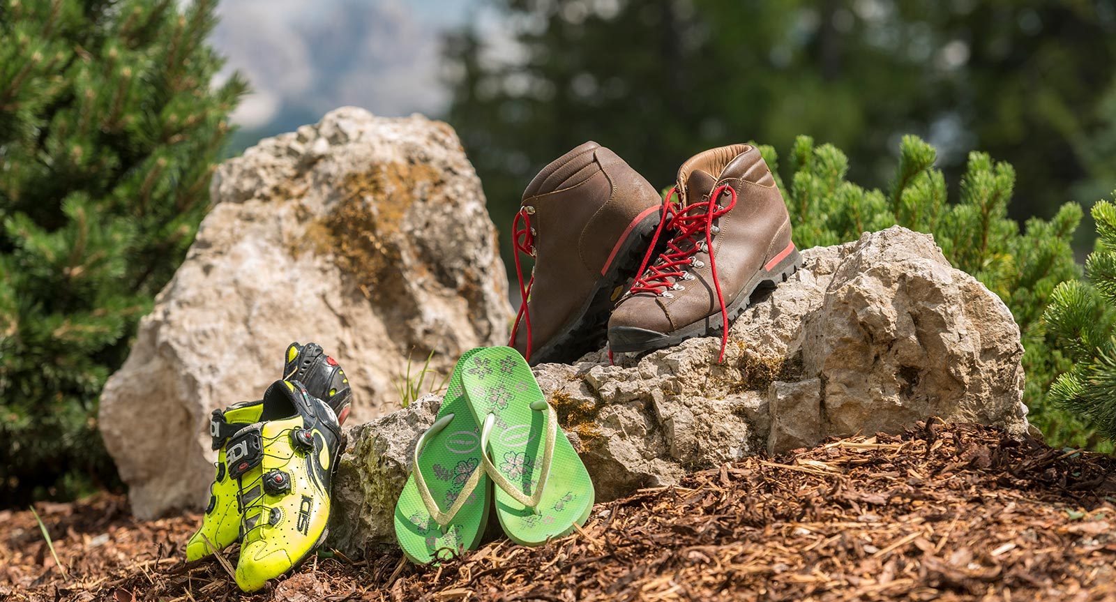 Cycling shoes, hiking shoes and flip flops placed outside next to a stone