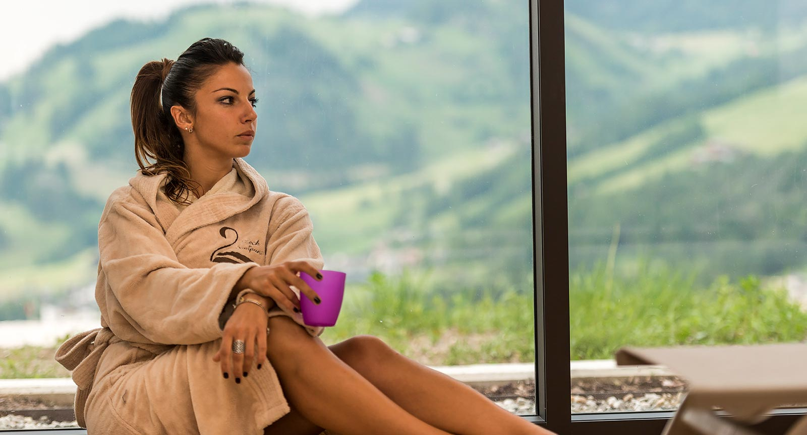 a young lady sits in the wellness area of the Lech da Sompunt with a cup in her hand