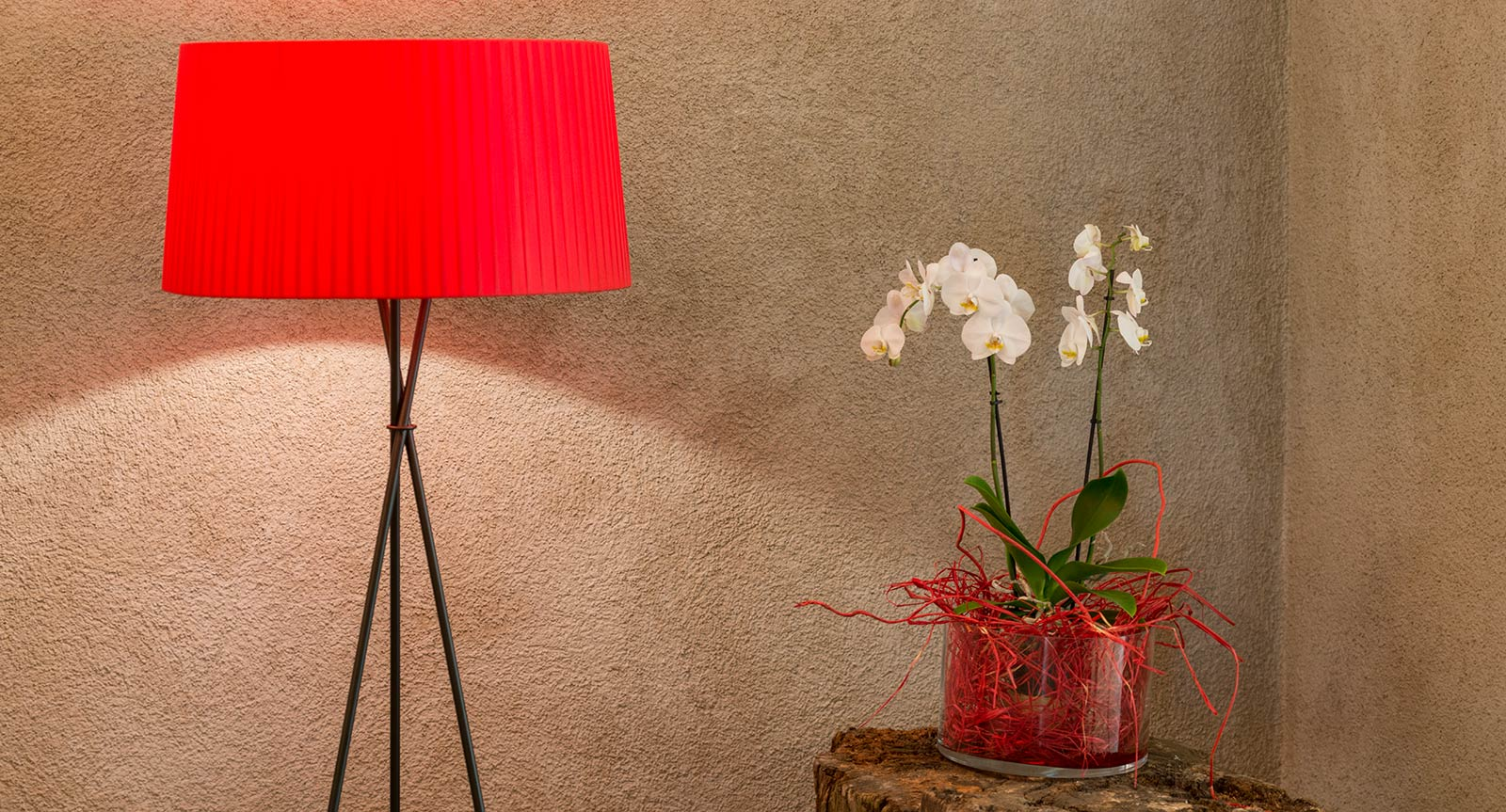a red lamp and a vase with white flowers in it on a night box