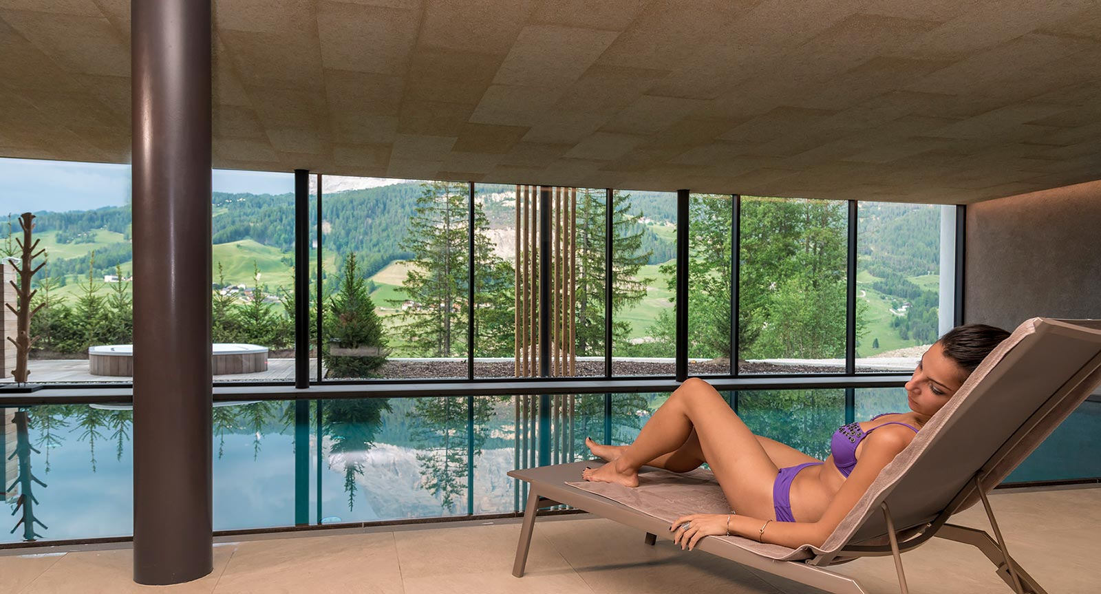 a lady in bikini on the deck chair next to the pool in the spa area of Lech da Sompunt in Alta Badia