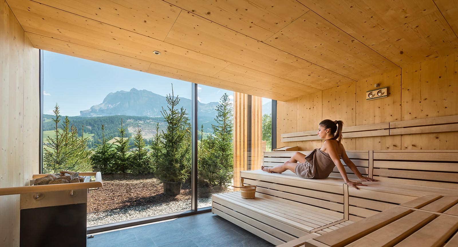 a lady sits with a towel in the sauna of Lech da Sompunt and enjoys the view of the surrounding mountains