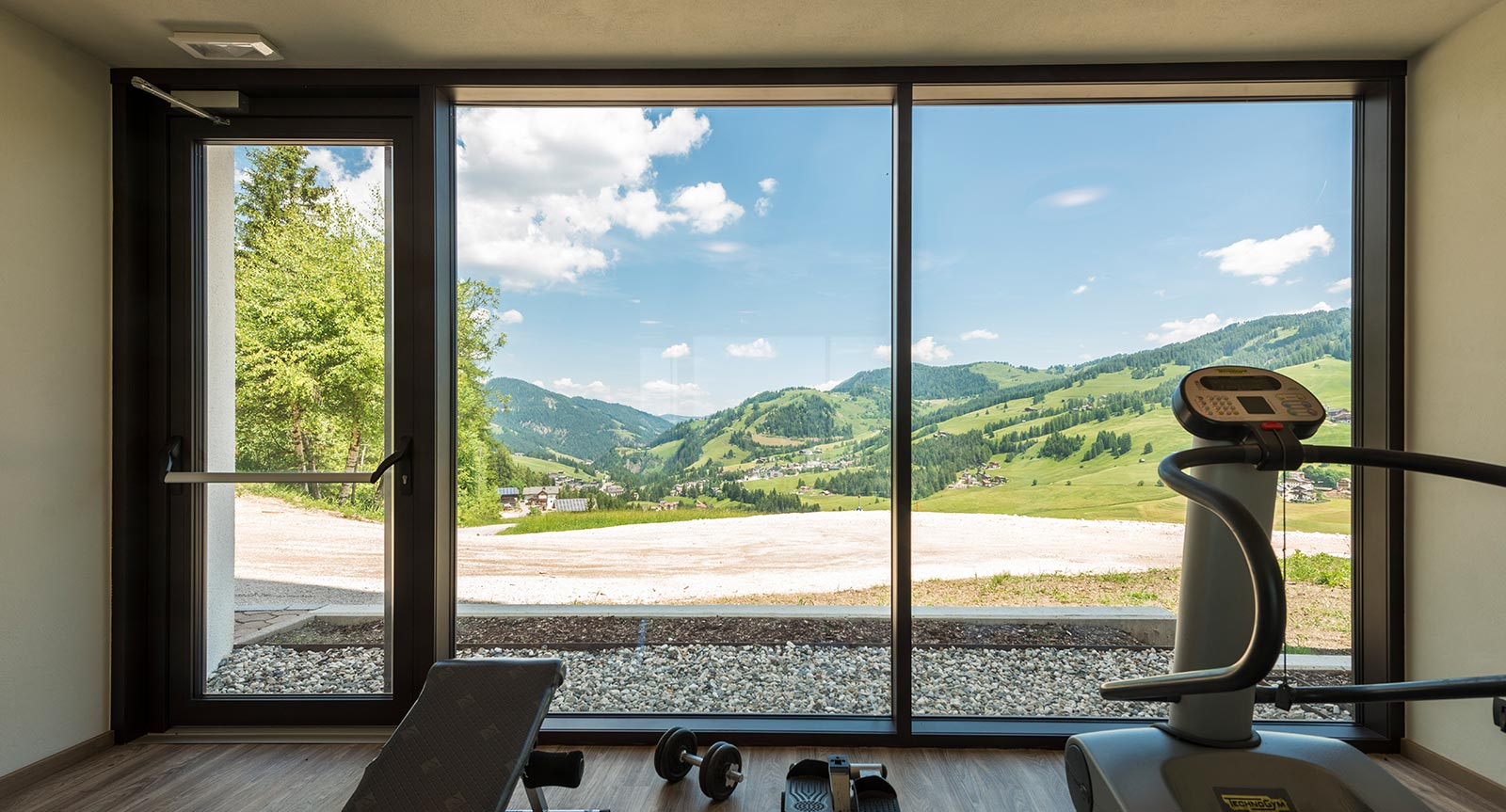 Fitness equipment in front of a panoramic window with a view of Val Badia
